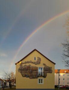 Blick aus der Kirche: Haus mit Lokomotive auf der Fassade und darüber einen doppelten Regenbogen.